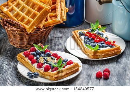 Waffles with fruit and whipped cream on wooden table