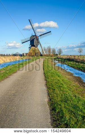 Colorful Dutch polder landscape with a restored wooden hollow post mill with a thatched lower housing originally built in 1795. It's a sunny day in the middle of the winter season.