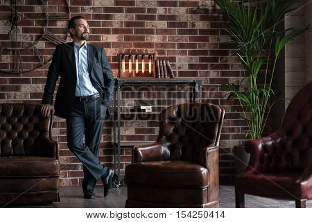 I am the boss. Confident handsome bearded man leaning on the sofa and crossing legs while standing in the study room