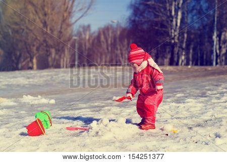 cute little girl digging snow, kids winter activities