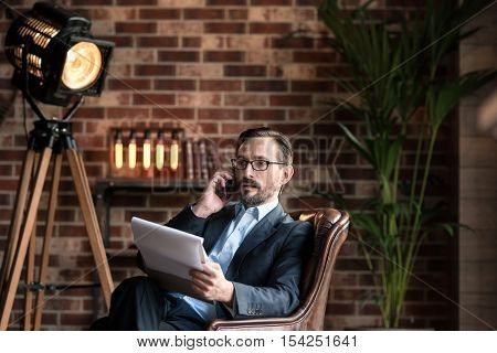 Being in control. Confident self employed stylish businessman sitting in the armchair and holding some sheets of paper while discussing business issues on the phone