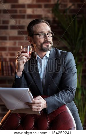 Helping to relax. Nice content bearded man leaning on the armchair and enjoying his whisky while holding some documents