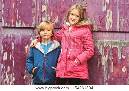 Portrait of two adorable kids outdoors, wearing warm coats standing next to old purple background
