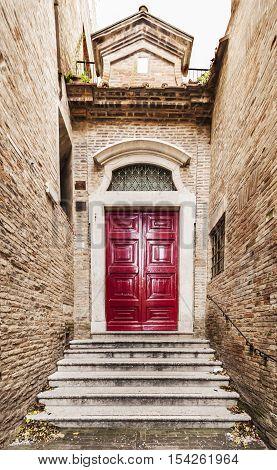 Old Italian red front door in Urbino, Italy