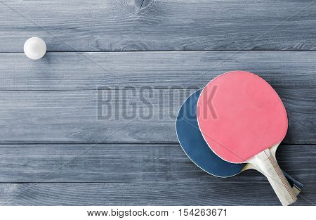 Table tennis racket on wooden board background