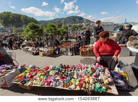 TBILISI, GEORGIA - OCT 16, 2016: Elderly woman selling handmade toys on outdoor market during city festival Tbilisoba on October 16, 2016. Tbilisoba is traditional festival in capital of Georgia from 1979