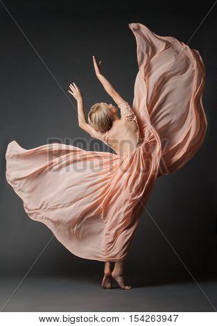 Young woman in light chiffon dress dancing on black plain .