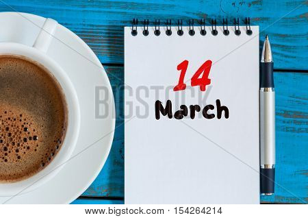 March 14th. Day 14 of month, calendar on blue wooden table background with morning coffee cup. Spring time, Top view.