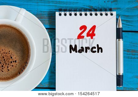 March 24th. Day 24 of month, calendar on blue wooden table background with morning coffee cup. Spring time, Top view.