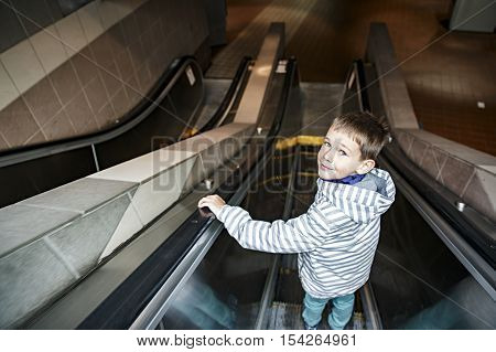 boy on the escalator in the metro. smiling child goes down the escalator in the subway. the concept of self-reliance of the child