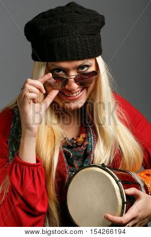 Young beautiful smiling blonde woman in colorful clothes black hat and sunglasses with a cheerful look holding small ethnic djembe drum at grey background