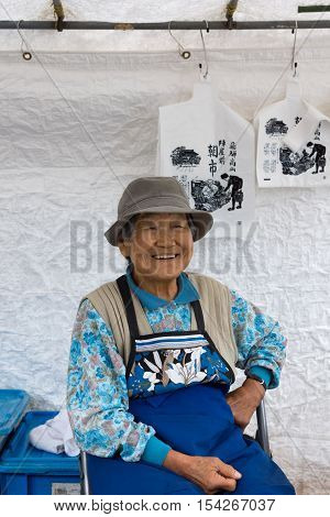 Takayama Japan - September 24 2016: Closeup of old smiling lady who is a vendor on the public morning market in front of the Jinya Hall. Blue clothes white tarp background.