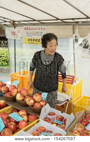 Takayama Japan - September 24 2016: Older active lady who is a vendor on the public morning market in front of the Jinya Hall promotes her red apples. Black clothes white tarp background.