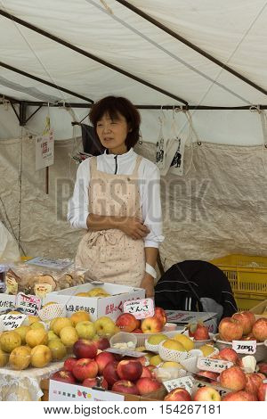 Takayama Japan - September 24 2016: Middle aged lady who is a vendor on the public morning market in front of the Jinya Hall promotes her red and yellow apples. Beige clothes white tarp background.