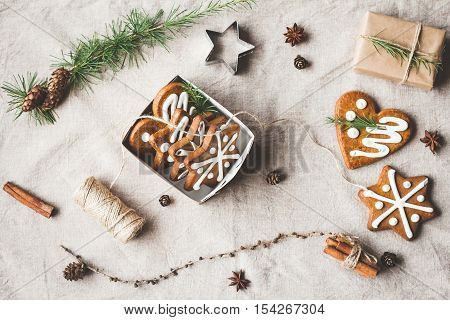 Christmas composition. Gift larch branches cinnamon sticks anise star christmas cookies. Top view flat lay
