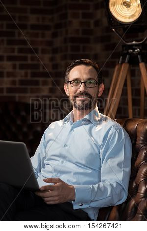I love my job. Nice cheerful joyful man holding a laptop and smiling while enjoying his work