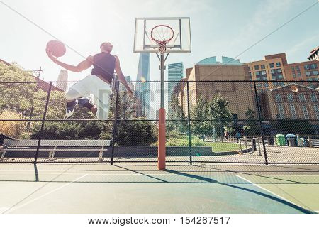 Street basketball athlete performing huge slam dunk on the court New york buildings background