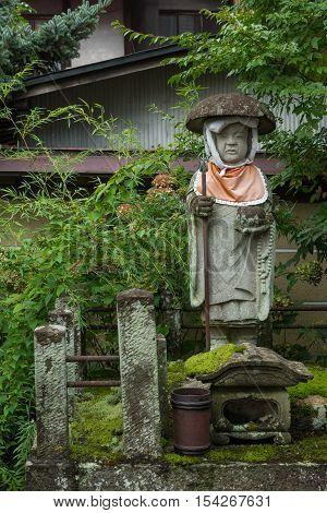 Takayama Japan - September 24 2016: Bodhisattva stone statue in garden of Hikakokubun-ji Buddhist Temple. Lots of green foliage and moss. Idol has red apron and a dome hat.