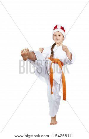 On a white background karateka in a cap of Santa Claus hits a kick leg
