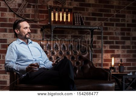 Being tired. Nice joyful attractive businessman holding his cell phone and drinking alcohol while relaxing after a working day