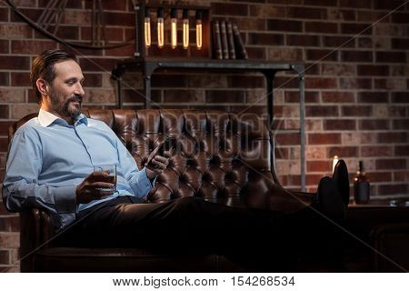 Comfortable position. Happy content stylish man putting his legs on the table and looking at his mobile phone while relaxing on the sofa
