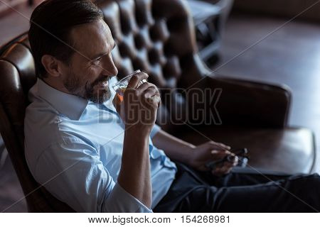 Reducing stress. Positive happy successful man holding a glass of whisky and smiling while enjoying his alcoholic drink