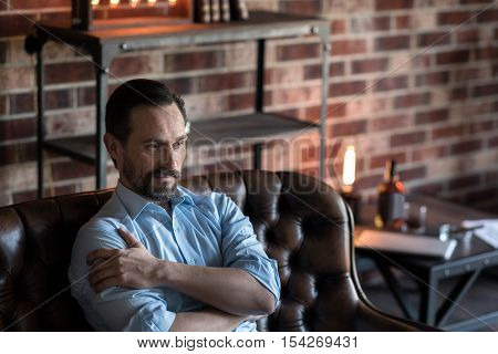 Body language. Good looking nice pleasant man sitting on the couch and wrapping his arms around him while thinking about something