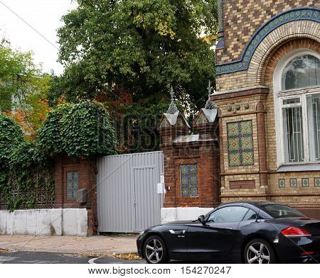 Black luxury BMW on the old street. Black luxury BMW and brick building of the 19th century. Luxury black BMW near the Brazilian Embassy in Moscow.