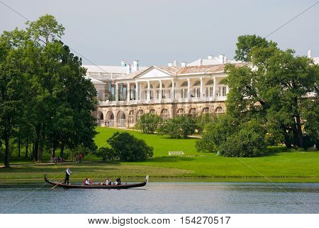 TSARSKOYE SELO, SAINT - PETERSBURG, RUSSIA - JULY 25, 2016: Gondolier and people in the gondola on The Great Pond in The Catherine Park. On the background is The Cameron Gallery