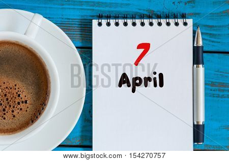 April 7th. Day 7 of month, calendar with morning coffee cup, at workplace. Spring time, Top view.