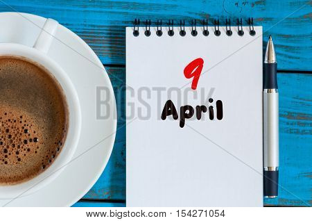 April 9th. Day 9 of month, calendar with morning coffee cup, at workplace. Spring time, Top view.