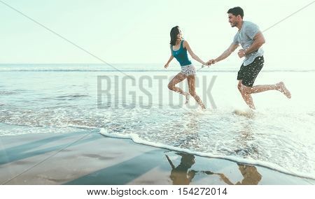Happy couple running in the sea splashing water