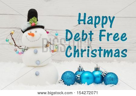Debt Free message Some snow Christmas ornaments and a snowman on weathered wood with text Happy Debt Free Christmas