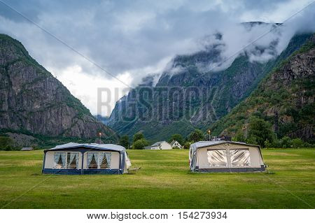 Camping field with camper tents under the rocky mountains of norwegian fjord. Eidfjord, Hordaland, Norway poster