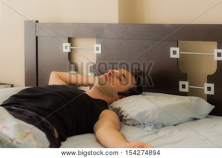 Man Comfortably Sleeping In His Bed In The Morning