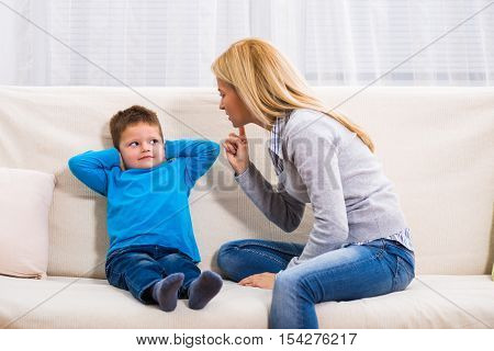 Photo of angry mother  scolding at her son.