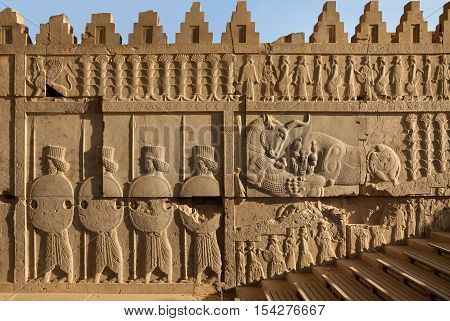 Bas relief carvings of a lion hunting a bull beside embossed soldiers on one of the staircases in Persepolis UNESCO World Heritage Site near Shiraz belonging to Achaemenid Empire 500 BC.