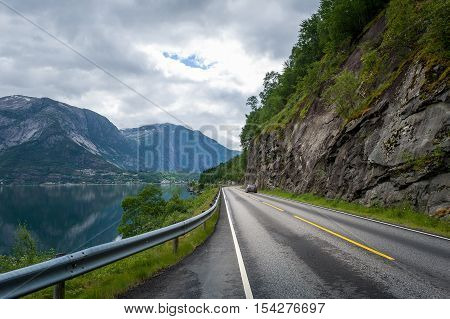 Beautiful road between fjord water and steep mountain with one car driving. Norwegian touristic routes. Eidfjord, Hordaland, Norway.