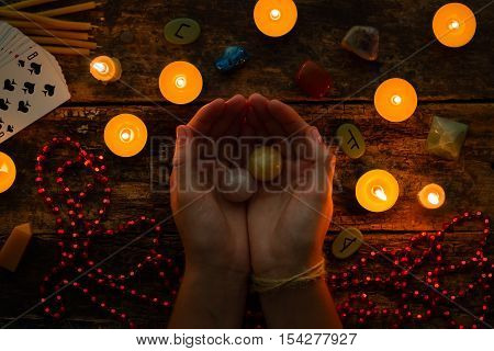 Fortuneteller Holds Crystal Balls For Divination Against A Background Of Candles And Runes