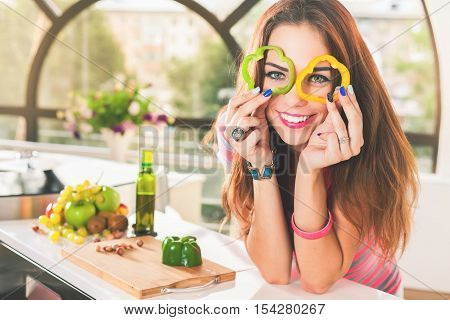 Attractive young woman keeps fresh pieces of bell pepper, vegetable salad at kitchen. Cooking. Diet, figure. Eating healthy food, vegetables ingredients. Recipe. Nutrition. Fruits at the table