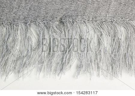 Fringe of grey knitwear fabric on white background. Close up