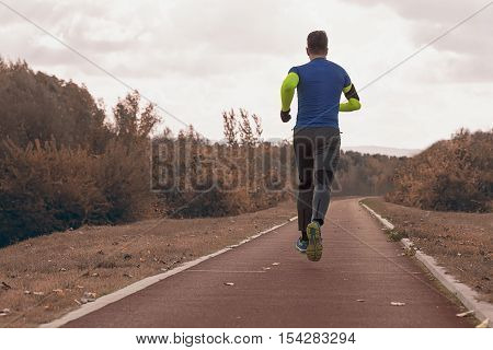 Jogging In The Park Autumn Edition. Young Man In Sports Clothing Jogging In Park