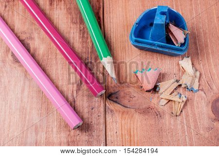 sharpener and pencils on the wooden background