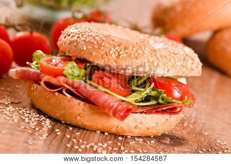 Sesame bagels with cherry tomatoes and pepperoni..