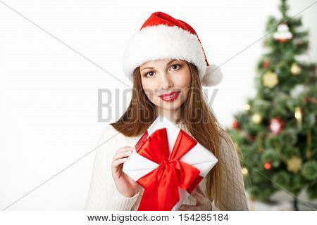 christmas, x-mas, valentine's day, celebration concept - smiling woman with gift box over white background and christmas tree