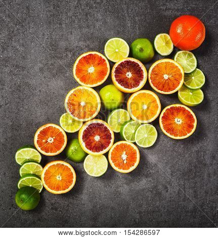 Slices of lime and blood orange fruits on grey stone background. Healthy eating and dieting concept. Copy space. Top view