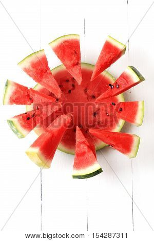 watermelon on a white wooden background top view half watermelon with flying In pieces