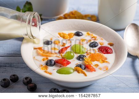 Pouring milk on cornflakes with fruits on wooden table