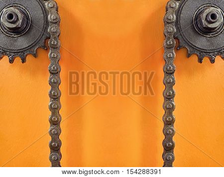 Cogwheels and double chain on orange background with empty space for text.Technology background.