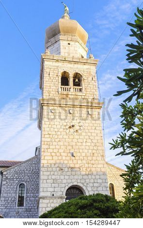 Bell tower of the cathedral the Church of the Assumption of Blessed Virgin Mary in Krk Croatia a monument of Romanesque era St. Quirinus and Barbara with a Venetian sculpture of an angel holding a trumpet on top.